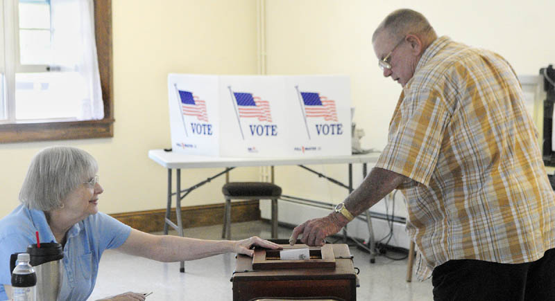 Ballot clerk Mary Haven, left, holds open the box as Bob Gleason drops in a ballot today, during the special Senate District 19 election at Pownalborough Hall in Dresden.
