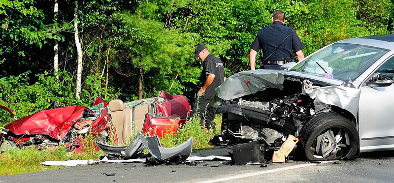 Kennebec County Sheriff's Department Sgt. Mike Pion, left, and Augusta Police Lt. Christopher Massey look over two of three cars involved in an accident today on the Route 3 connector, between Riverside Drive and North Belfast Avenue in Augusta.