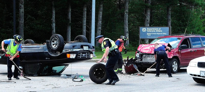 Augusta Police and Togus fire department crews clean up at the scene of a two-vehicle collision at gate to VA Maine Healthcare System hospital at Togus, on Eastern Avenue and Spring Road, this afternoon in Augusta.