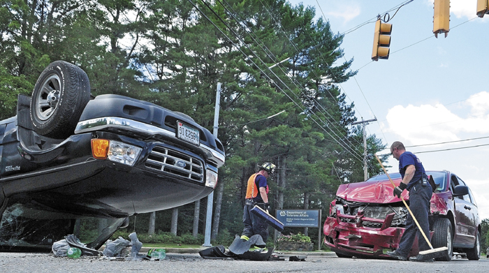 Togus firefighters clean up at the scene of a two-vehicle collision at the gate to VA Maine Healthcare System hospital at Togus this afternoon, in Augusta.