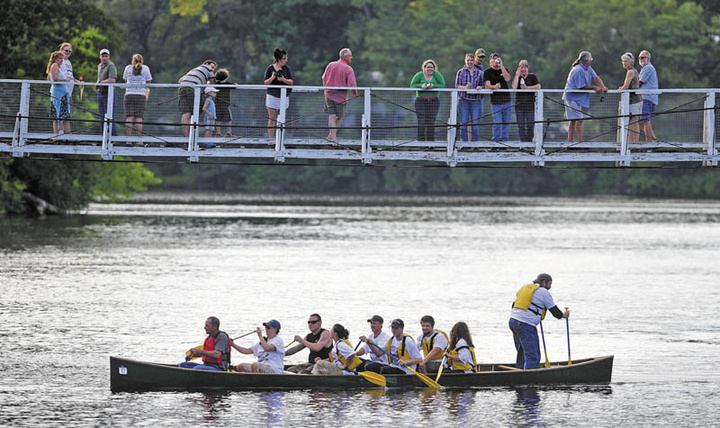 Team New Balance crosses the finish line at the suspension bridge in the Skowhegan River Fest boat races on the Kennebec River Thursday.