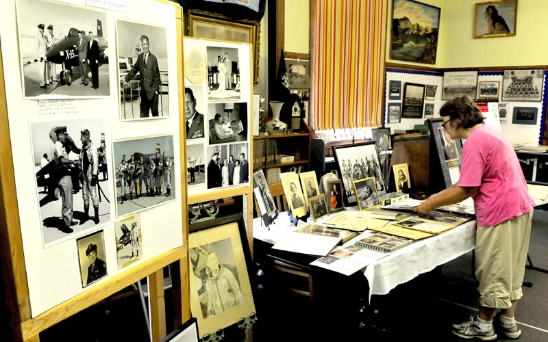 Elizabeth Ackroyd looks over photographs and memorabilia of Air Force Major Robert Rushworth at the Madison Historical Society on Thursday. The exhibit is part of the Madison-Anson Days event.