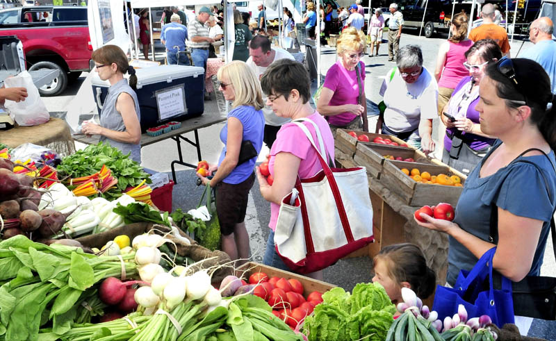 Customers, including Sharon Bushey, center, wait in line to buy fresh produce at the booth of Cornerstone and Fail Better farm, in Palmyra, at the Waterville Farmers Market on Thursday.