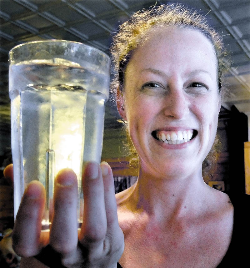 """Amber Strickland holds a glass of water from the Bingham water supply at Thompson's Restaurant recently. Strickland said she has lived all over New England, and Bingham's water is the best tap water she has had. """"We have never heard a complaint from customers,"""" she said."""