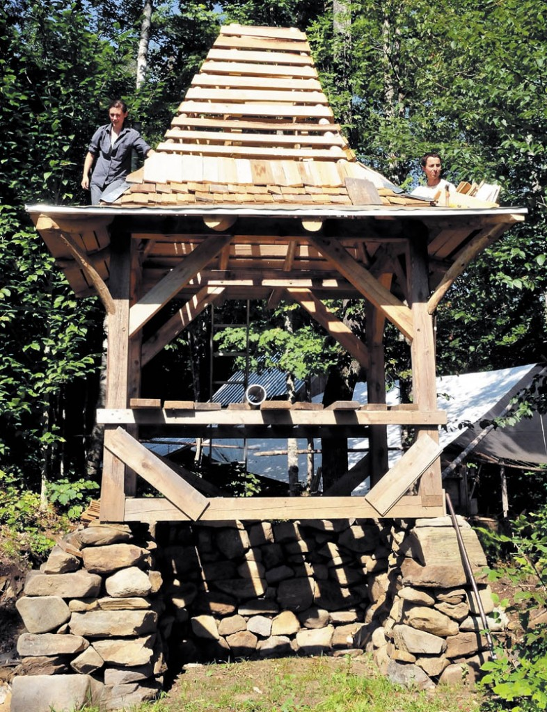 Ashley Hardy and Chris Knapp build a new composting outhouse at the Koviashuvik Living School in Starks recently.