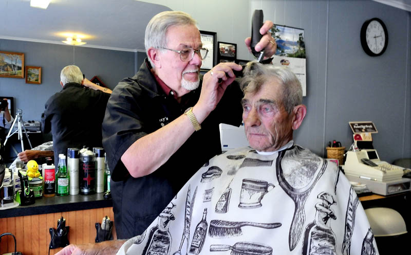 "Freeman ""Buzzy"" Buzzell cuts the hair of customer Ron Frazier at his shop on Main Street in Madison recently. Buzzell said he has been a barber for nearly five decades and enjoys his customers and meeting new ones."