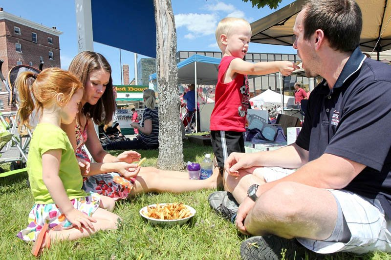 Liam Rose, 3, shares a French fry with his dad Phil while eating lunch with his sister Isabelle, 4, and mom Heather at the Taste of Greater Waterville on Wednesday.