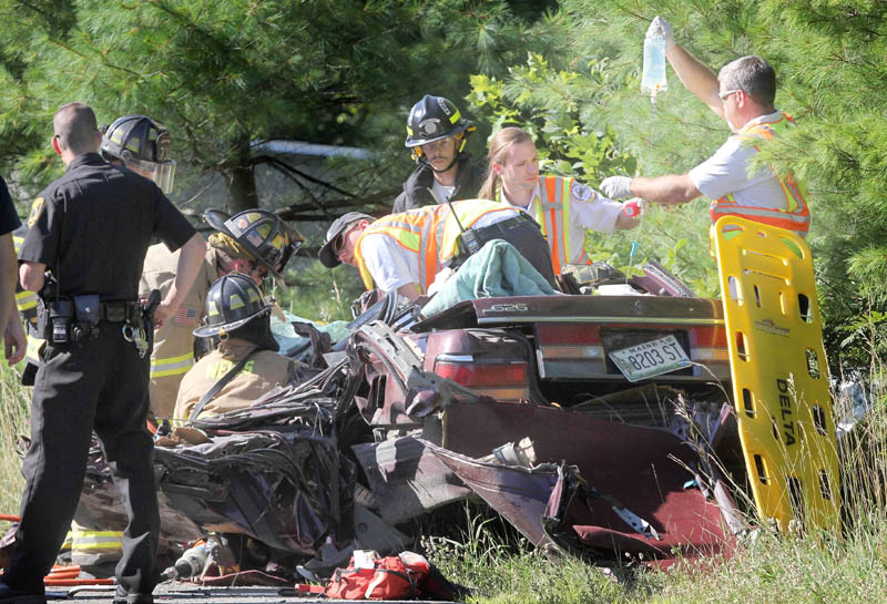 Rescue officials work to remove a female occupant of a vehicle involved in a head-on collison on China Road in Winslow on Wednesday afternoon.