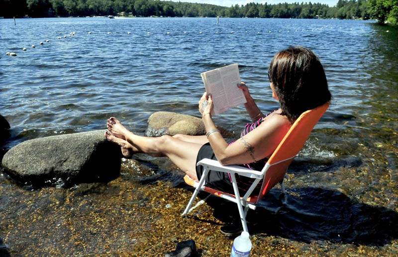 Laurie Bushey soaks her feet in Messalonskee Lake in Oakland while reading a book on a warm Thursday.