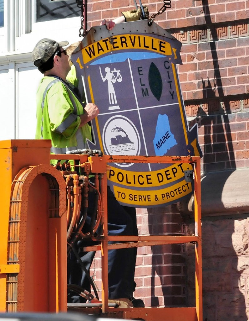 David Main, left, and Jacob Chambers of the Waterville public works department remove the Waterville Police Department sign on City Hall on Aug. 1. City councilors on Tuesday will consider spending $85,000 to renovate the former headquarters of the department, to allow for expansion of other departments to the space.
