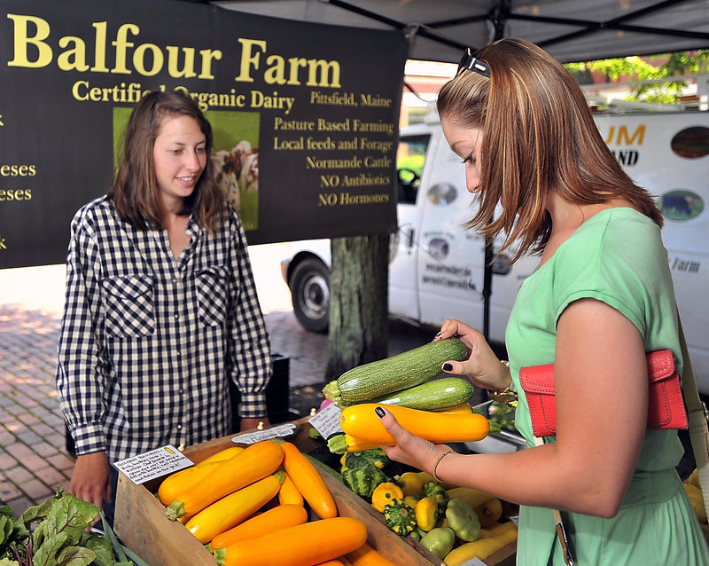 Hannah Brilliant, left, answers questions about her produce from Limington resident Michelle Twomey at the farmers market in Monument Square last month. Brilliant, who runs an organic vegetable farm in Pittsfield, says she is fielding many more questions from consumers this year about genetically modified organisms.