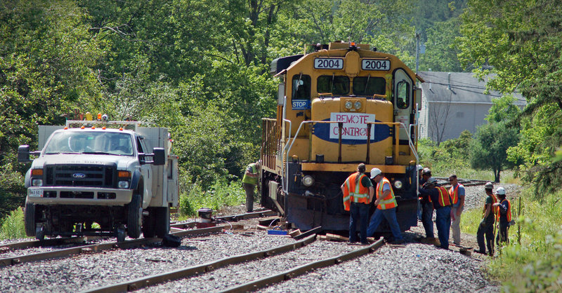 "A derailed Montreal, Maine & Atlantic Railway train displays a ""remote control"" sign Wednesday in Brownville. Trains carrying a single engineer must display the sign and they sometimes are operated by remote control."