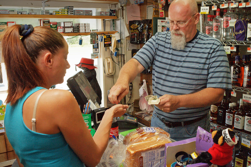 "Steve Johnson, above, owner of the General Store & More on Route 11 in Brownville, makes change for Tammy Laythe on Wednesday. Johnson said revenue at the store has fallen. ""Everything has slowed down a bit,"" he said."