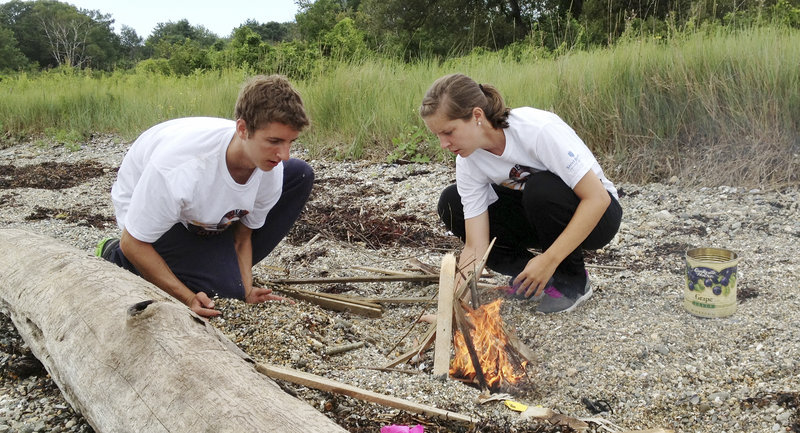 """Brianna Russell of Falmouth, right, and Tyler Sym of Lexington, Mass., start a fire without matches or accelerant as part of a """"Survivor""""-like exercise on Friday that employed practical and intellectual skills at a camp called Science Island Extreme."""