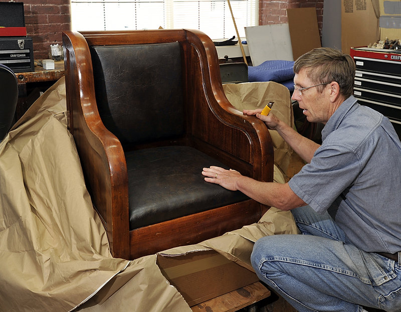 Jon Brandon unwraps a chair to be conserved by his Brunswick company, East Point Furniture Conservation.