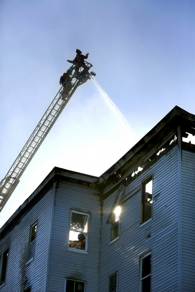 Maine Sunday Telegram file photo/Tim Greenway Firefighters spray water on the roof of a vacant apartment building on Bartlett Street in Lewiston on May 6. The building was razed after being destroyed by the arson fire.