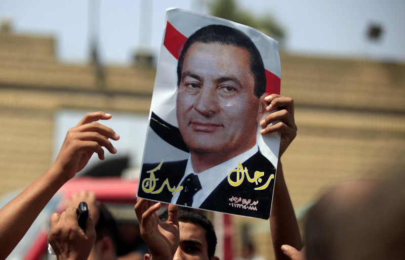 A supporter of Egypt's deposed President Hosni Mubarak holds a poster of him in Cairo on Thursday.