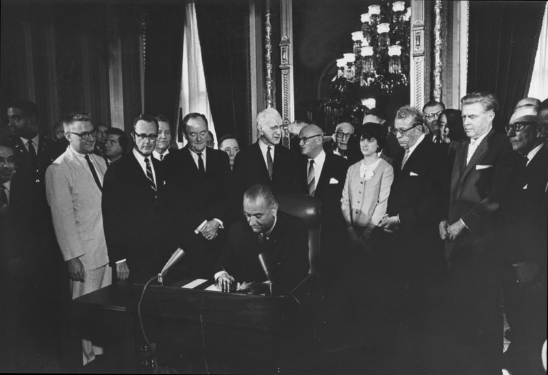 President Lyndon Johnson signs the Voting Rights Act of 1965, two years after the March on Washington, surrounded by members of Congress. At left behind the man in the light-colored suit, looking away from LBJ, is associate press secretary Harold Pachios of Cape Elizabeth, who later was a founding partner at a Portland law firm.