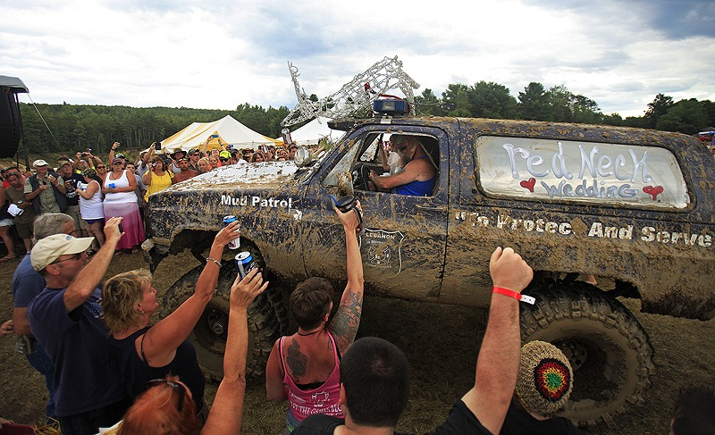 Fans of the Redneck (Blank) Games, formerly the Redneck Olympic Games, in Hebron cheer as a monster truck carrying Lucretia Blais to her wedding with Jeff Gould arrives at the main stage Saturday. A production team from the History Channel chronicled the festivities.