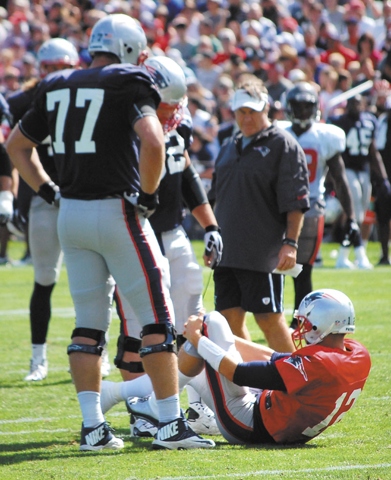 OH, NO: New England Patriots quarterback Tom Brady grabs his left knee, while left tackle Nate Solder, left, and head coach Bill Belichick look on after Brady suffered what a source said was a sprained left knee during a joint workout with the Tampa Bay Buccaneers on Wednesday in Foxborough, Mass.