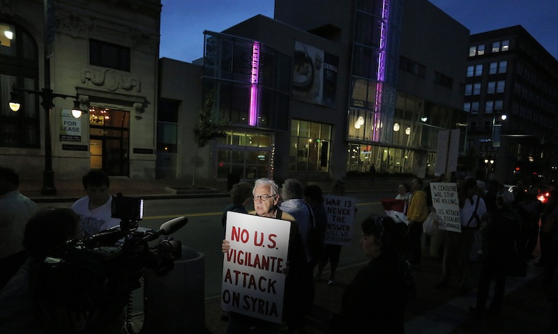 Wells Staley-Mays of Portland, who has visited Syria, holds a sign while conducting a television interview during a gathering in Monument Square on Monday evening, Sept. 9, 2013, to protest proposed military action in Syria by the United States.