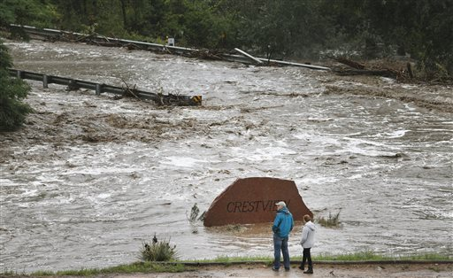Local residents look over a road washed out by a torrent of water following overnight flash flooding near Left Hand Canyon, south of Lyons, Colo., on Thursday.