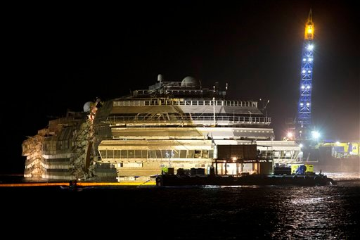 "The Costa Concordia is seen after it was lifted upright, on the Tuscan Island of Giglio, Italy, early Tuesday morning. The crippled cruise ship was pulled completely upright early Tuesday after a complicated, 19-hour operation to wrench it from its side where it capsized last year off Tuscany, with officials declaring it a ""perfect"" end to a daring and unprecedented engineering feat."