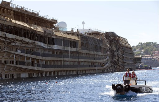 People take a small boat past the damaged side of he Costa Concordia on the Tuscan Island of Giglio, Italy, last week. The crippled cruise ship was pulled completely upright early last Tuesday after a complicated, 19-hour operation.