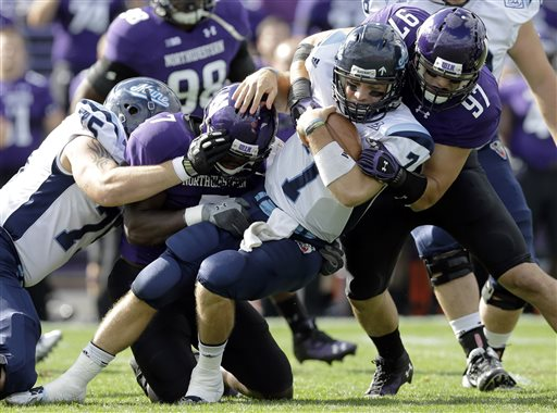 HANGING IN: Maine quarterback Marcus Wasilewski (7) is tackled by Northwestern defensive end Ifeadi Odenigbo (7) and Tyler Scott (97) during the Black Bears' 35-21 loss Saturday in Evanston, Ill.