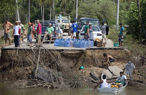 People stand on the edge of a collapsed bridge as they wait to ferry their goods via a boat across the Papagayos River, south of Acapulco, near Lomas de Chapultepec, Mexico, on Wednesday.