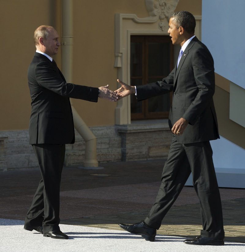 President Barack Obama reaches to shakes hands with Russia's President Vladimir Putin during arrivals for the G-20 summit at the Konstantin Palace in St. Petersburg, Russia on Thursday, Sept. 5, 2013. (AP Photo/Pablo Martinez Monsivais/Pool)