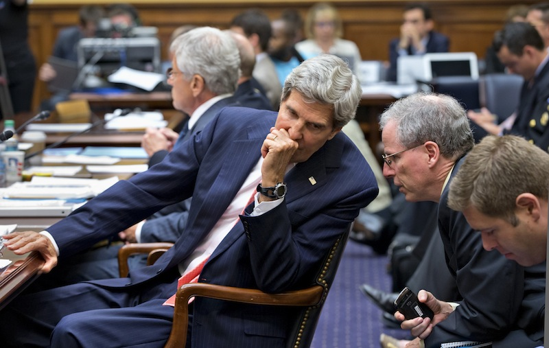 Secretary of State John Kerry confers with U.S. Ambassador to Syria Robert Ford, right, on Capitol Hill in Washington, Wednesday, Sept. 4, 2013, during a House Foreign Affairs Committee hearing on President Barack Obama's request for congressional authorization for military intervention in Syria, a response to last month's alleged sarin gas attack in the Syrian civil war. Defense Secretary Chuck Hagel sits at left. (AP Photo/J. Scott Applewhite)