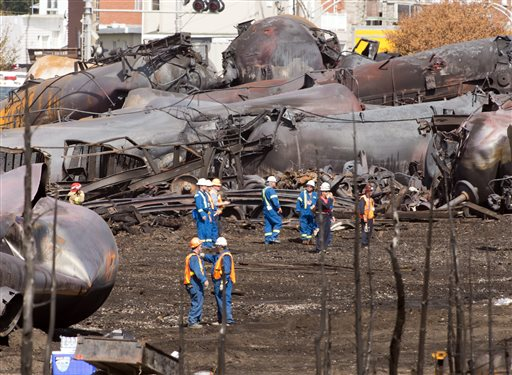 Workers stand before mangled tanker cars Tuesday, July 16, 2013, at the crash site of the train derailment and fire in Lac-Megantic, Quebec. The July 6 crash left 47 people dead and 40 buildings destroyed. (AP Photo/Ryan Remiorz, pool)