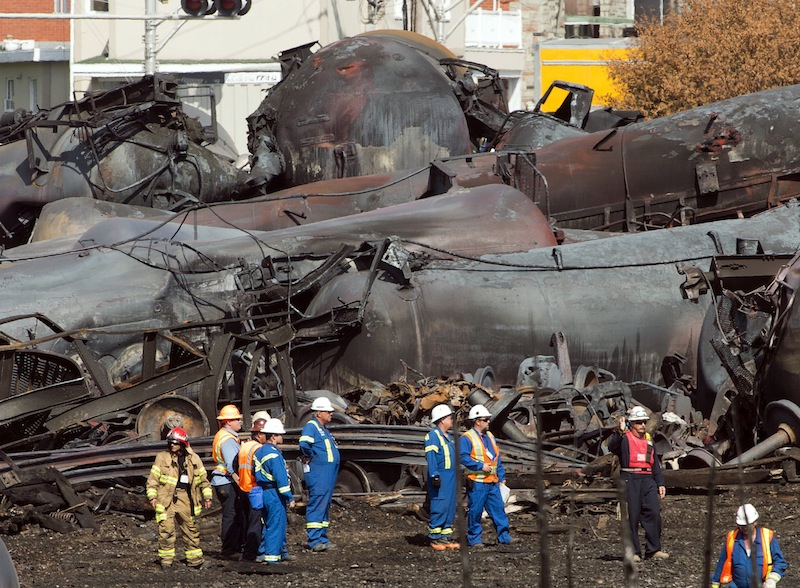 In this Tuesday, July 16, 2013 file photo, workers stand before mangled tanker cars at the crash site of a train derailment and fire in Lac-Megantic, Quebec, that happened on July 6. The bankrupt railroad whose runaway train sparked a fire and explosion that killed 47 people in Quebec could be sold by year's end, the company's trustee said Thursday.. (AP Photo/Ryan Remiorz, Pool, File)