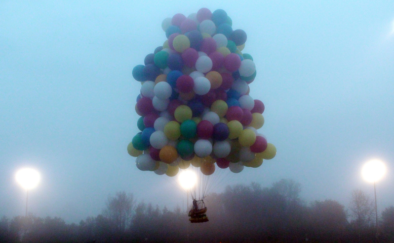A balloon cluster carrying Jonathan Trappe lifts off from Caribou on Thursday. Unlike a conventional hot-air balloon, Trappe is relying on hundreds of helium-filled balloons clustered together.