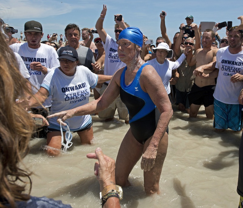 In this Monday, Sept. 2, 2013 file photo provided by the Florida Keys News Bureau, Diana Nyad emerges from the Atlantic Ocean after completing a 111-mile swim from Cuba to Key West, Fla. Nyad's swim from Cuba to Florida has generated some skepticism in the small community of marathon swimmers. Critics have suggested that during a speedy stretch of the 53-hour swim, Nyad might have gotten into or held onto the boat that accompanied her. They also question whether she violated the traditions of her sport by relying on a specialized mask and wetsuit to protect herself from jellyfish. Nyad's navigator and one of the swim's official observers tell The Associated Press that Nyad didn't cheat. (AP Photo/Florida Keys Bureau, Andy Newman, File)