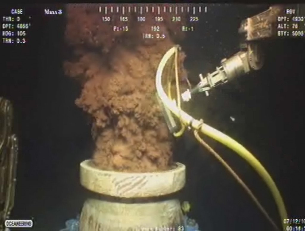 In this July 12, 2010, image from a video made available by BP PLC, oil flows out of the top of the transition spool, which was placed into the gushing wellhead and housed the containment cap, at the site of the Deepwater Horizon oil spill in the Gulf of Mexico.