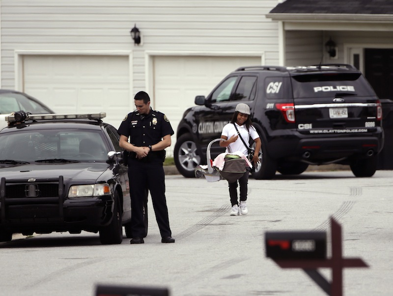 A woman carrying a baby walks past a Clayton County police officer standing guard Wednesday, Sept. 18, 2013, near a house where 14-year-old Ayvani Hope Perez was kidnapped Tuesday during a home invasion, in Ellenwood, Ga. The FBI and the Georgia Bureau of Investigation were assisting Clayton County police in the massive search for the teen. (AP Photo/John Bazemore)