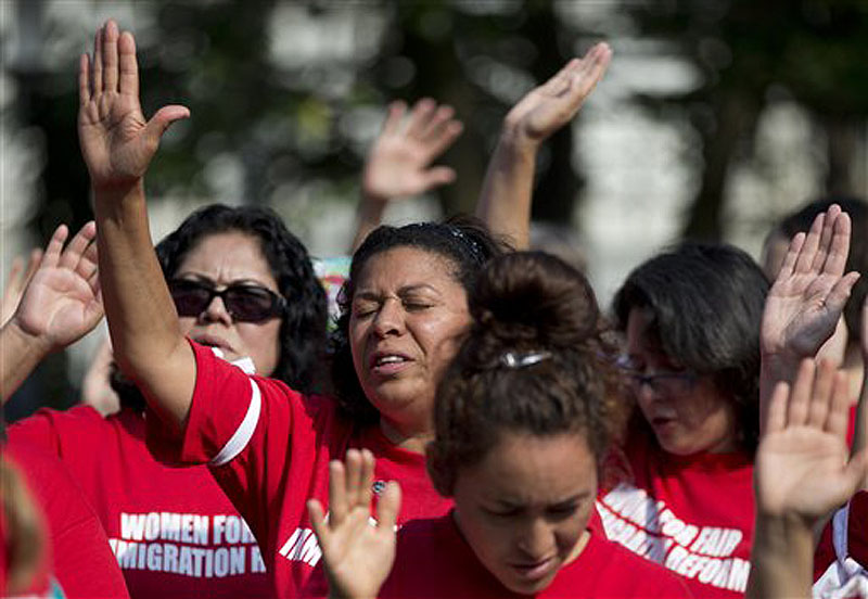 "Women recite the ""Oath for a House United"" as they gather before blocking an intersection outside the House of Representatives on Capitol Hill in Washington on Thursday to protest Congress' inaction on immigration reform."