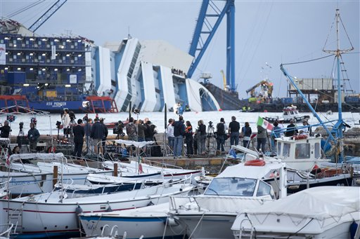 Reporters watch the Costa Concordia ship lying on its side on the Tuscan Island of Giglio, Italy, early Monday morning. An international team of engineers is trying a never-before attempted strategy to set upright the luxury liner, which capsized after striking a reef in 2012, killing 32 people.