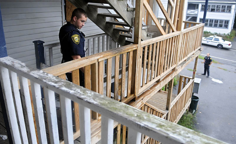 Augusta Police Officers Niko Hample, left, and Ben Murtiff search an apartment building Thursday on Jefferson Street that was closed by the City of Augusta. The Augusta City Council is considering a proposed rental housing standard for General Assistance recipients. The building was closed after several code violations were discovered, according to police.