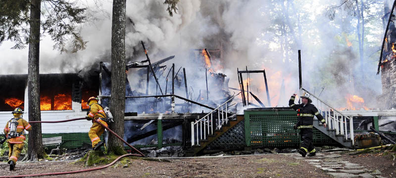 FIrefighters approach the Echo Lake Lodge Tuesday in Fayette. Rented as a private camp, the Lodge that was erected in 1937 was destroyed by fire.