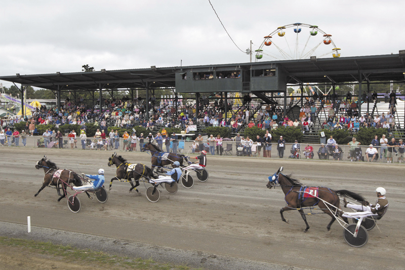 Harness race horses cross the finish line at the Windsor Fair in Windsor. The state's casinos were supposed to help harness-racing tracks by funneling some of the proceeds to them, allowing them higher payoffs to keep horsemen from leaving the state. Instead, race tracks are struggling more than ever because wagering on horse races has fallen off as patrons migrate to casinos.
