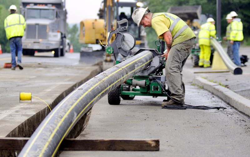 Workers with Bowdoin Excavation lay gas pipes in July in Augusta for Maine Natural Gas.