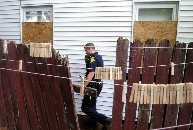 Augusta Police Officer Niko Hample walks the perimeter of an apartment building Thursday on Jefferson Street that was closed by the City of Augusta.
