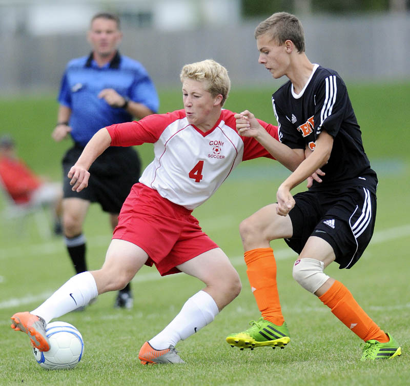 DRIVE: Cony High School's Conner Perry, left, moves the ball away from Brewer High School's Gehrig White during a soccer game Tuesday in Augusta.