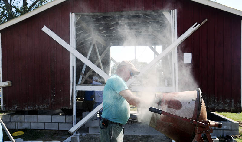 Greg Larravee adds concrete to a mixer Wednesday for the foundation of the black smith shop that volunteers at the Litchfield Fair are placing before the annual agricultural exhibition.