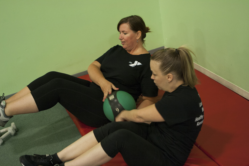 Marie Moore, left, works out with a weighted ball under the guidance of trainer Kimberly Gagne at the Kennebec Valley YMCA recently.