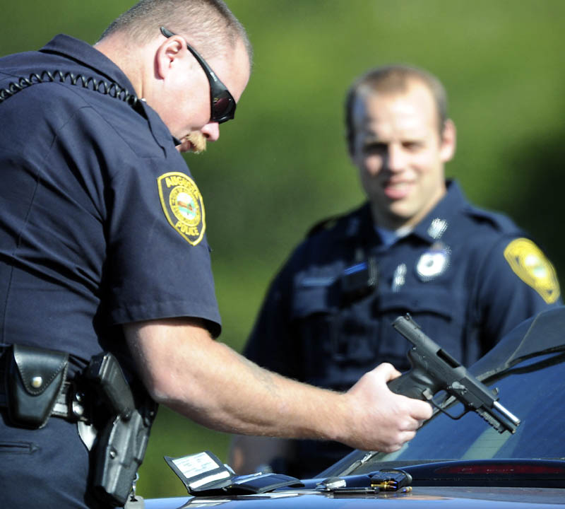 Augusta Police Department Sgt. Chris Shaw inspects a pistol Tuesday that officers took from a man following a road rage incident in Augusta. A man allegedly displayed the pistol after two woman confronted him about his driving, according to police.