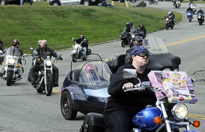 Bikers drive through Augusta today during the 32nd annual United Bikers of Maine Toy Run. Hundreds of motorcycles cruised in a caravan through Central Maine en route to the Windsor Fairgrounds to donate toys they collected.